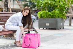 Mulher asiática que olha o assento cor-de-rosa de compra do saco Foto de Stock