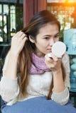 Mulher asiática que olha o espelho na cafetaria Imagem de Stock Royalty Free