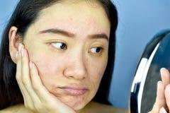 Mulher asiática que olha si mesma no espelho, sentimento fêmea para irritar sobre sua mostra da aparência da reflexão o sinal fac foto de stock royalty free