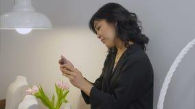 Mulher asiática que olha a tela do smartphone e que sorri em uma sala de visitas video estoque
