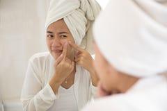 Mulher asiática que pressiona a acne em seu mordente Imagens de Stock