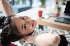 Mulher asiática que relaxa e que olha a câmera ao sentar-se no escritório Foto de Stock Royalty Free