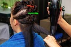 Mulher asiática que seca o cabelo do cliente com champô no cabeleireiro Beauty Salon imagens de stock royalty free