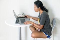 Mulher asiática que senta-se em uma tabela com portátil Imagens de Stock Royalty Free