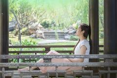 A mulher asiática que senta-se na cadeira de madeira no parque público para relaxa o tempo fotografia de stock royalty free