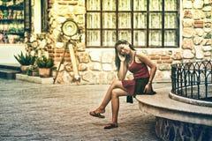 Mulher asiática que senta-se no banco de pedra na cidade foto de stock