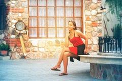 Mulher asiática que senta-se no banco de pedra na cidade fotos de stock