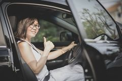 Mulher asiática que senta-se no banco do condutor tumb do suspiro do carro do suv no bom imagens de stock royalty free