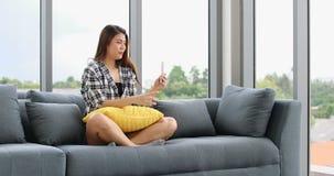 Mulher asiática que senta-se no sofá e que usa o smartphone filme