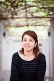 Mulher asiática que sorri com as árvores verdes no fundo foto de stock royalty free