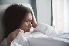 Mulher asiática que tem a dor de cabeça em sua cama migraine Doença, disea Imagens de Stock