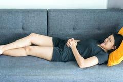 A mulher asiática que tem a dor de estômago dolorosa no quarto após acorda, sofrimento fêmea dos grampos abdominais do período da fotos de stock royalty free