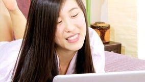 Mulher asiática que tem o divertimento que conversa com amigo vídeos de arquivo