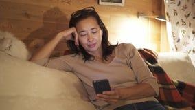 Mulher asiática que texting na cama video estoque