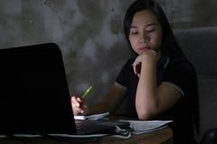 Mulher asiática que trabalha da casa atrasada no trabalho noturno no conceito de iluminação pobre a luz escura tem alguns grão e  fotos de stock royalty free