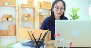 A mulher asiática que trabalha em casa, negócio novo começa acima com negócio em linha ou conceito do SME filme