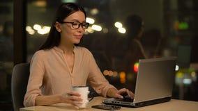 Mulher asiática que trabalha no portátil, café bebendo para ser acordado e inspirado na noite vídeos de arquivo