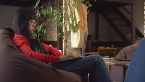Mulher asiática que trabalha no portátil no sótão com escadas de madeira video estoque
