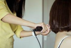 A mulher asiática que usa ferros do cabelo com endireitamento, fecha-se acima foto de stock royalty free