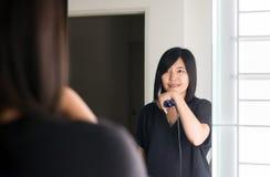 Mulher asiática que usa ferros do cabelo com endireitamento na sala imagens de stock