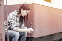 Mulher asiática que usa o dispositivo moderno do smartphone no trem foto de stock royalty free