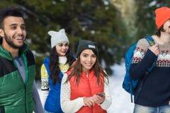 Mulher asiática que usa o inverno exterior de passeio do grupo esperto de Forest Happy Smiling Young People da neve do telefone foto de stock royalty free