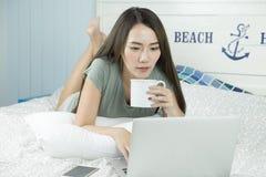Mulher asiática que usa o portátil e bebendo o café ao encontrar-se em sua cama fotografia de stock royalty free