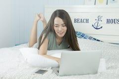 A mulher asiática que usa o portátil e vê a mensagem no smartphone ao encontrar-se em sua cama fotos de stock royalty free