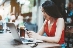 Mulher asiática que usa o smartphone e o portátil na barra da rua fotografia de stock