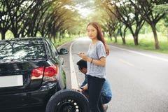 Mulher asiática que usa o telefone celular ao olhar e homem forçado que senta-se após uma divisão do carro na rua fotos de stock