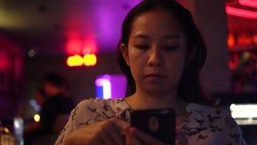 Mulher asiática que usa o telefone esperto no clube noturno moderno de néon vermelho vídeos de arquivo
