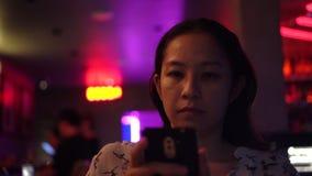 Mulher asiática que usa o telefone esperto no clube noturno moderno de néon vermelho video estoque