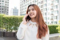 Mulher asiática que usa o telefone esperto no fundo borrado do residenti fotos de stock royalty free