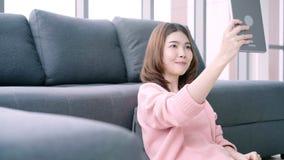 Mulher asiática que usa a tabuleta ao encontrar-se no sofá home em sua sala de visitas Tabuleta fêmea feliz do uso para a chamada video estoque