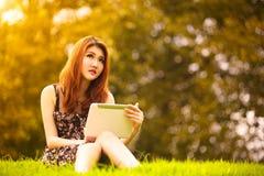 Mulher asiática que usa a tabuleta digital no parque Foto de Stock Royalty Free