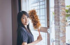 Mulher asiática que usa uma escova da poeira, mãos da empregada doméstica, espanando Imagem de Stock