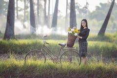 Mulher asiática que veste a cultura tailandesa tradicional, no campo, estilo do vintage foto de stock