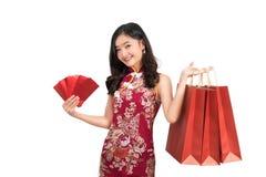 Mulher asiática que veste envelopes vermelhos e saco de compras da posse chinesa do vestido imagem de stock