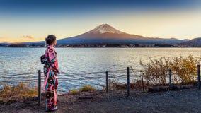Mulher asiática que veste o quimono tradicional japonês na montanha de Fuji Por do sol no lago Kawaguchiko em Japão Foto de Stock