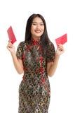 Mulher asiática que veste o vestido preto que guarda o presente do dinheiro Imagens de Stock