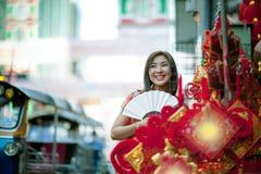 Mulher asiática que veste a roupa chinesa da tradição com a cara de sorriso toothy do fã de bambu chinês na cidade da porcelana d imagens de stock