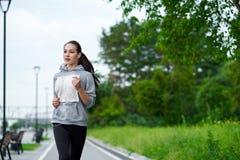 Mulher asiática running na margem Movimentar-se da manhã Os trens do atleta fotografia de stock