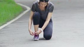 Mulher asiática running que amarra laços dos tênis de corrida vídeos de arquivo