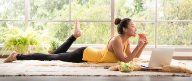 Mulher asiática saudável que encontra-se no assoalho que come a salada que olha relaxado e confortável imagens de stock
