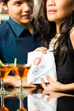 A mulher asiática seduz o homem no restaurante Imagem de Stock