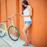 A mulher asiática 'sexy' que estão perto da parede e o vintage bicycle Imagens de Stock Royalty Free