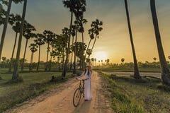 A mulher asiática vestiu-se na caminhada vietnamiana tradicional da bicicleta no fundo do por do sol imagem de stock royalty free