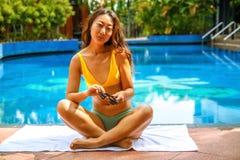 Mulher asi?tica bonita que relaxa na piscina no hotel fotos de stock