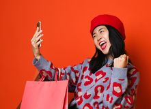 A mulher asi?tica em uma boina e em uma camiseta ? moda, com um saco de compras colorido faz um selfie trabalhador no telefone ap fotos de stock royalty free
