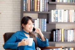 A mulher asi?tica nova do retrato bonito que sorri usando o telefone esperto m?vel que fala para apreciar e beber o caf? com rela imagens de stock royalty free